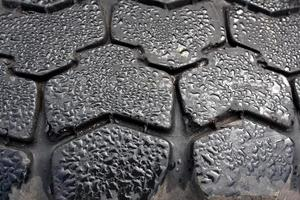 Raindrops on tyre closeup.