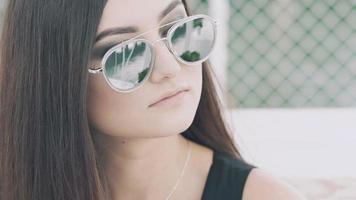 close-up de uma garota segurando uma taça de coquetel e olhando para trás
