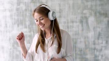 linda garota com fone de ouvido branco dançando na sala