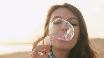 ragazza che soffia bolle sulla spiaggia video