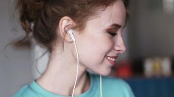 menina bonita dançando e ouvindo música. olhando para a câmera.