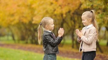 Little adorable girls having fun at warm day in autumn park outdoors
