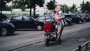 Mother hold little son on hands on street. Family. Summer. Baby carriage
