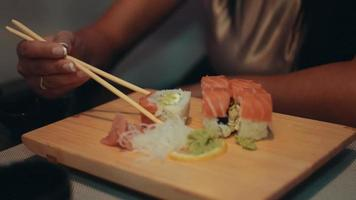 Brunette girl sitting at table in restaurant. Smile. Eat sushi by chopsticks video