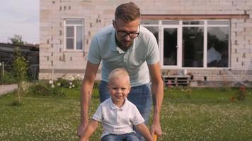 pai feliz se divertindo com seu filho pequeno e sorridente no jardim