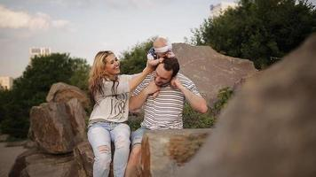 padres jóvenes felices jugando y riendo con su pequeña hija en el verano al atardecer. concepto de familia