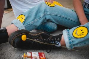 Augsburg, Germany, 2020 - Close-up of a person in jeans with smiley faces on them