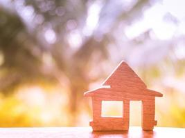 Wooden home model on colorful bokeh