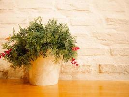 Flower in pot on wooden table white brick wall background photo