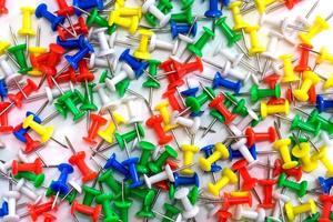 chinchetas de colores sobre fondo blanco foto