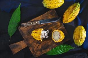 Cut cocoa fruit on a wooden chopping board.