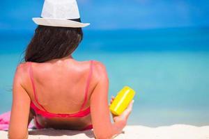 Mujer sosteniendo la botella de protector solar en la playa foto