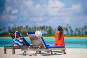 Woman sitting on  a  lounge chair on a  beach photo