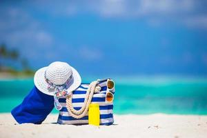 Beach bag with sunglasses, sunscreen, and a hat
