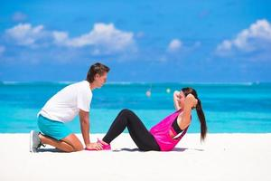 Man holding a woman's feet while doing crunches on a beach