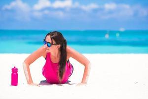 Woman doing push-ups on a beach