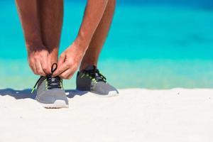 Hombre atar los zapatos en la playa