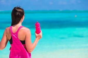 mujer hidratando en la playa