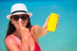 mujer sosteniendo una botella de protector solar foto