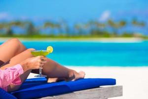 Close-up of a person holding a cocktail on a beach