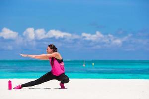 Mujer haciendo ejercicios en una playa blanca