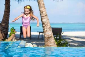 niña saltando a una piscina