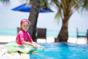 niña sentada junto a una piscina