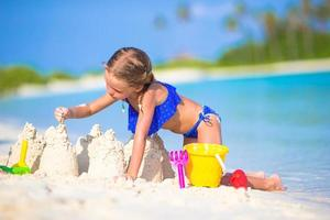 niña construyendo un castillo de arena en arena blanca foto