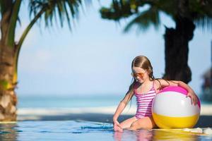 niña con una pelota de playa en la piscina