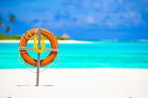 Orange lifebuoy on a white beach