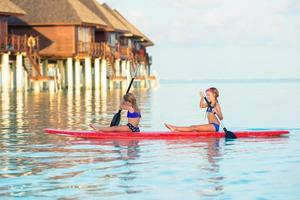 Maldives, South Asia, 2020 - Two girls paddleboarding at a resort