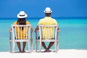 Couple sitting in white chairs on a beach photo