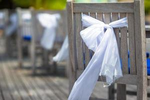 Wooden chairs with white bows photo