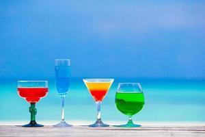 coloridos cócteles contra un océano azul foto