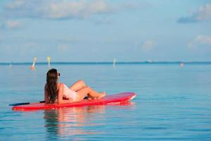 mujer relajante en una tabla de surf