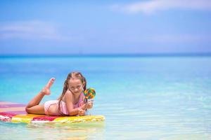 niña con piruleta en una tabla de surf