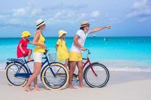 Family riding bicycles on a tropical beach