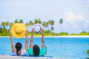 Couple holding hats at a beach photo