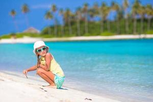 Girl playing in sand at the beach photo