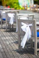 Wedding chairs decorated with white bows at outdoor cafe