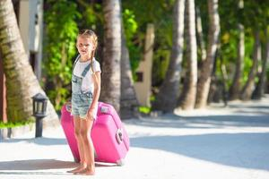 Girl with luggage with trees in the background