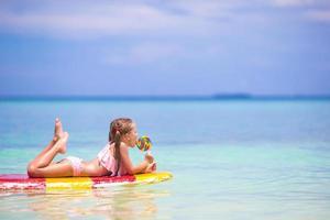 niña con una paleta en una tabla de surf en el mar