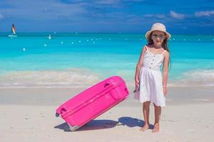 Girl with a pink suitcase on a white beach