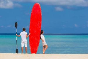 Couple with a paddleboard at the beach