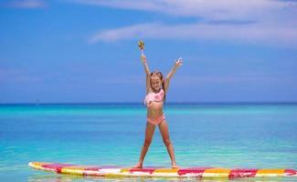 niña de pie sobre una tabla de surf