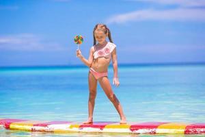 niña sosteniendo una paleta en una tabla de surf