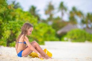 niña jugando en la arena de la playa foto