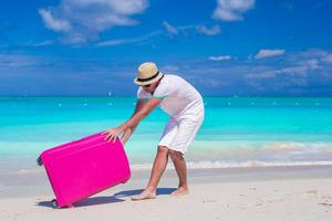 Man pulling luggage in the sand
