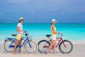 Couple walking with bikes on a beach