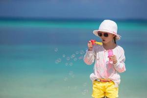 Girl having fun blowing bubbles on the beach